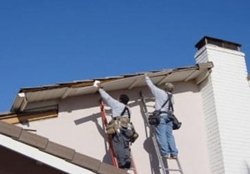 Men on ladders repairing part of roof