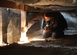 Man under house inspecting for termites